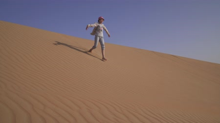 arap : Girl teenager runs around the sand on the slope of the dune in the Rub al Khali desert United Arab Emirates stock footage video Stok Video