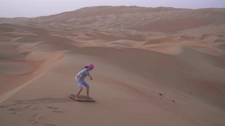 kumul : Teenage girl rolls on a sandboard on the slope of a dune in the Rub al Khali desert United Arab Emirates stock footage video