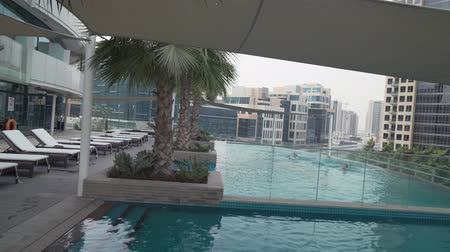 cityskyline : Dubai, UAE - April 07, 2018: Outdoor pool with beautiful views of downtown Dubai in Damac Maison Dubai Mall Street stock footage video