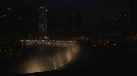 largest city : Dubai, UAE - April 08, 2018: Dubai Fountain is the worlds largest choreographed fountain system on the Burj Khalifa Lake at night stock footage video Stock Footage