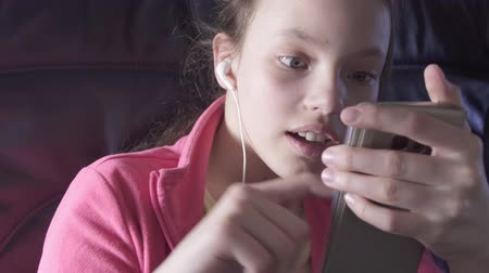 recinto : Cheerful teenage girl plays a game on a smartphone in the cabin of the plane while traveling stock footage video