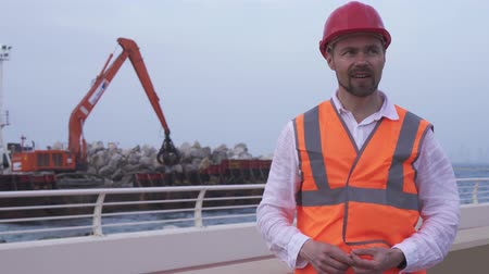 vasalás : Man in a helmet, architect, engineer, manager tells about the course of repair work of the coastline with a stone stock footage video