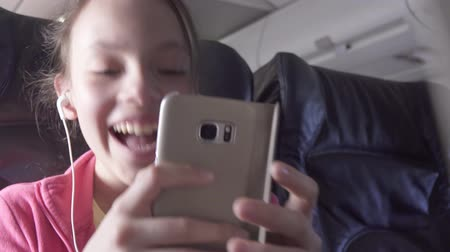 şartlar : Cheerful teenage girl plays a game on a smartphone in the cabin of the plane while traveling stock footage video