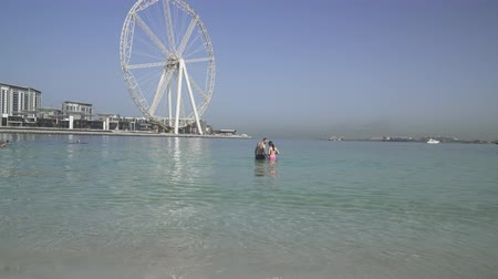cayan tower : Dubai, UAE - April 01, 2018: Tourists are swimming in clear water on Marina beach in Dubai stock footage video