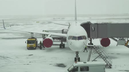 kazahsztán : Astana, Kazakhstan - March 30, 2018: Service of the aircraft preparation for flight at a snowy aerodrome of Astana International Airport stock footage video Stock mozgókép