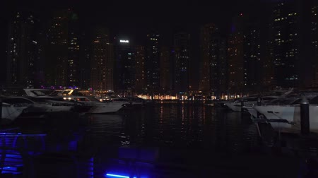 scraper : Dubai, UAE - April 01, 2018: Night view of the harbor with yachts in the expensive tourist area Dubai Marina stock footage video Stock Footage