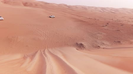 arábie : Off-road cars with tourists descend from a high dune in the Rub al Khali desert stock footage video Dostupné videozáznamy