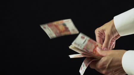bin : Female hand scatter five thousand rubles banknotes on a black background slow motion stock footage video