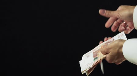 feixes : Female hand scatter five thousand rubles banknotes on a black background slow motion stock footage video