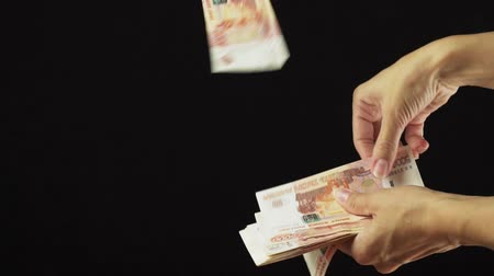 mille : Female hand scatter five thousand rubles banknotes on a black background slow motion stock footage video
