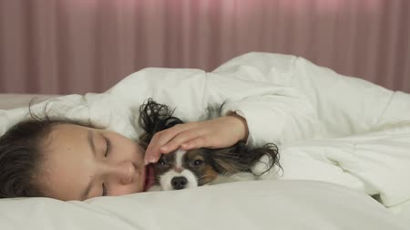 uykulu : Happy teen girl communicates with dog Papillon in the bed stock footage video