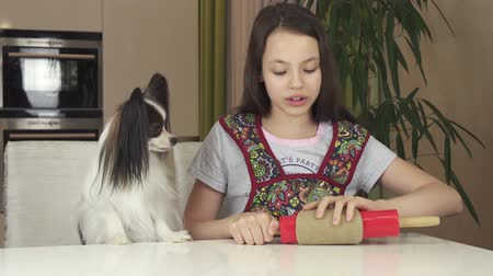 chefs table : Teen girl and dog Papillon prepare cookies, rolling dough with a rolling pin stock footage video Stock Footage