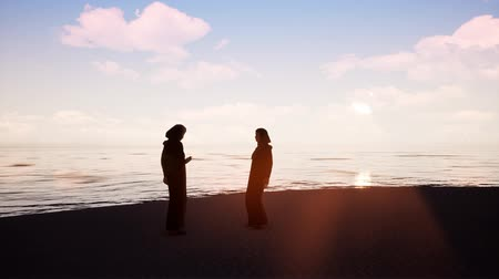 Two women in hijabs talking to each other by the ocean Stock Footage