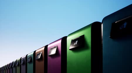 separado : A colored row of iron garbage bins against a clear blue sky. Waste sorting and saving the environment. Stock Footage