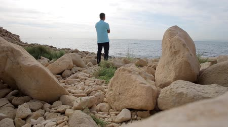 remotely : A man stands on the shore of the Mediterranean Sea among the stones and looks at the horizon Stock Footage