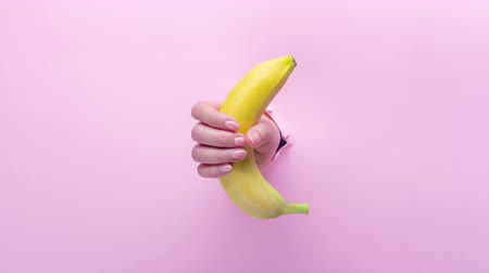 szakadt : A woman holds a banana in her hand, inserted through a hole in torn pink paper, 4k video Stock mozgókép