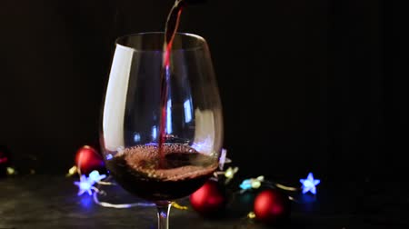 goblet : Pouring red wine in a glass on the dark festive background with colorful bokeh