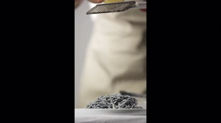 пармезан : Vertical video, chef rubs hard cheese on the black pasta, concept of typical Italian cuisine