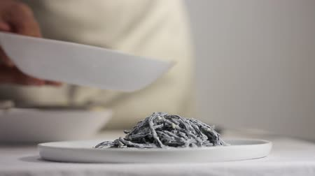 cuttlefish : Chef laying out black cuttlefish ink paste with carbonara sauce on a porcelain plate
