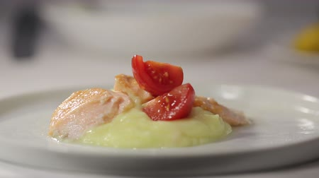 omega : Cooks hand puts a piece of red tomato on a plate with potato puree and decorate with thyme Stock Footage