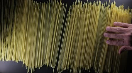 vermicelli : Man puts golden color raw spaghetti pasta on the dark black background