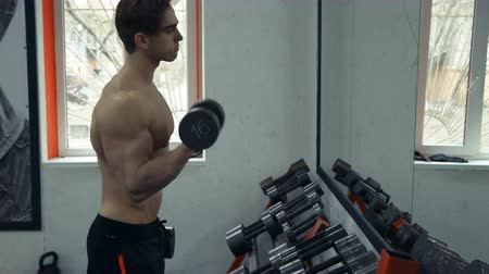 retouched : Muscular bodybuilder guy doing exercises on biceps with dumbbells in gym Stock Footage