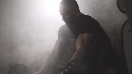 retouched : Muscular bodybuilder guy doing exercises on biceps with dumbbell in the gym, smoke on background. Slow motion
