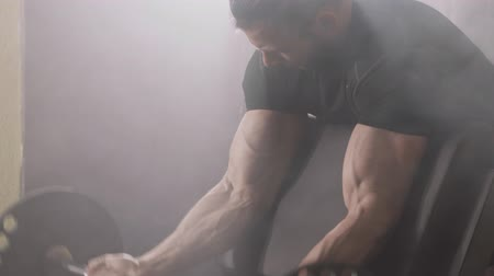 retouched : Muscular bodybuilder guy doing exercises on biceps with dumbbell in the gym, smoke on background Stock Footage