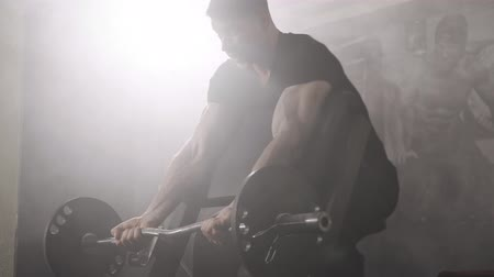 male : Strong Young Muscular Male Bodybuilder Exercising Biceps with Big Dumbbell at Gym. Smoke
