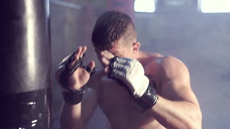 lutador : Young male boxer hitting punching bag, smoke on background. Slow motion. Stock Footage
