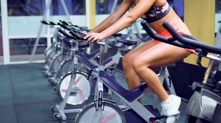 bicycle : Beautiful Blonde Female on gym bike doing cardio exercise. Stock Footage