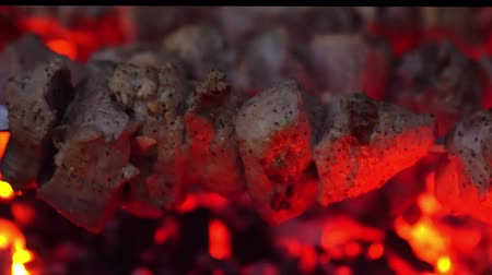 coals : Grilled kebab cooking on metal skewer. Roasted meat cooked at barbecue. BBQ fresh beef meat chop slices. Traditional eastern dish, shish kebab. Grill on charcoal and flame, picnic, street food
