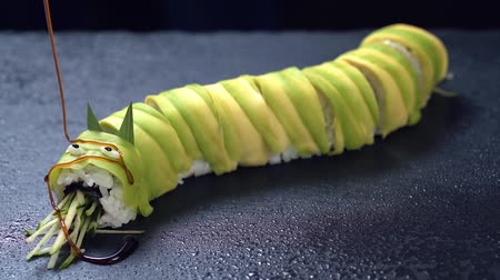 jikry : Sushi roll pour sauce on a dark stone background. Traditional Japanese dish. SLow motion. Dostupné videozáznamy