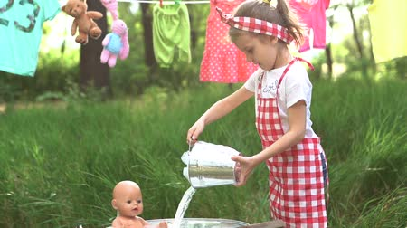 verificador : Cute girl in checkered dress headband washing toys in basin and looking at hands outdoors