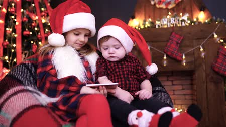 сестры : Two children, boy and girl in Christmas decorations playing smartphone