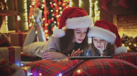 mother and daughter wearing pajamas and santa hats lying on the bed and watching tablet in the Christmas decorations Stockvideo