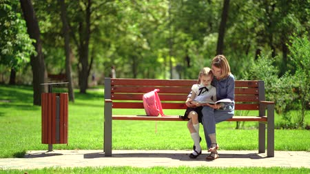 na : Mother and little daughter in outdoors public park sitting on the bench and read book, study lessons. Parenthood and child concept. Mother kissing her child.