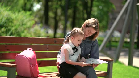 after school : Mother and little daughter in outdoors public park sitting on the bench and read book, study lessons. Parenthood and child concept. Mother kissing her child.