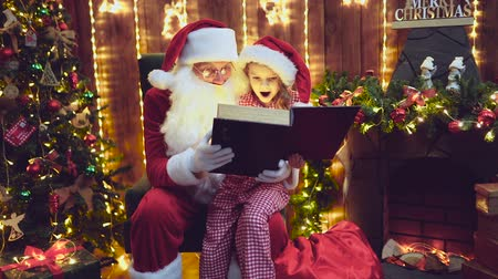 miraculous : Santa Claus open and read magic book with little cute amazed girl in pajama