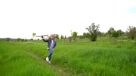 летчик : Little girl launches a toy plane into the air in the park outdoor. Child launches a toy plane. Beautiful little girl running on the grass and launches a pink toy plane. Slow motion