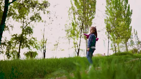 Little girl launches a toy plane into the air in the park outdoor. Child launches a toy plane. Beautiful little girl running on the grass and launches a pink toy plane. Slow motion