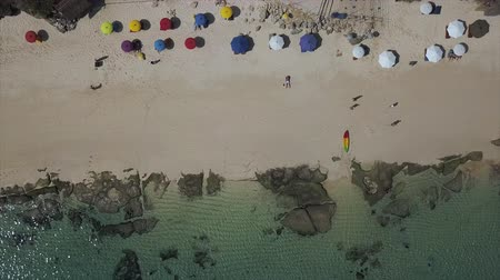 lagos : Beach with white sand and blue water, colorful umbrellas and kayak. Static shooting with the drone on top Stock Footage