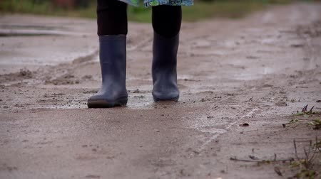difficults : on the bumpy road in the village there is a man in rubber boots Stock Footage