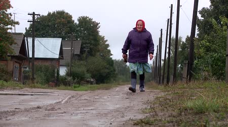 difficults : the old woman goes on a bumpy road in the village of in rubber boots in the rain