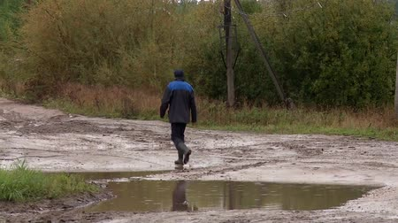 difficults : man avoids the puddle on the village street