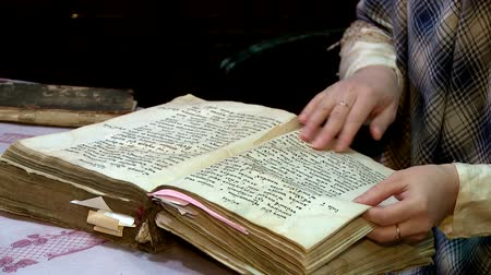 biblia : a woman flips through the pages of an old book