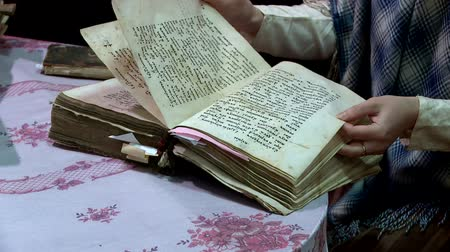 scrapbook : a woman flips through the pages of an old book
