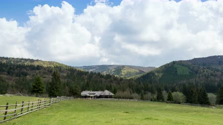 dağ evi : green valley between mountains with cottage in the spring Stok Video