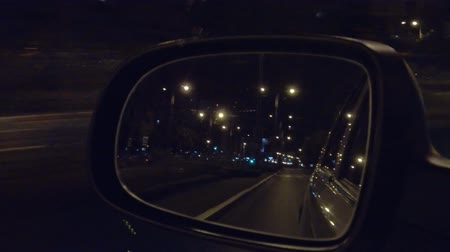 mirror of car driving on a night city road Стоковые видеозаписи