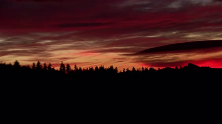 sunrise light : Dramatic autumn sunset with colorful clouds over the mountains with forest Stock Footage